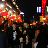 People eat while walking near Qianmen street in Beijing on Wednesday ahead of the Lunar New Year celebrations. | REUTERS