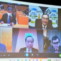 Prefectural governors from across the nation and Taro Kono, the minister in charge of the vaccine rollout (lower right), hold a video conference Wednesday to discuss how vaccines will be made available. | POOL / VIA KYODO