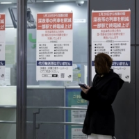 Notices are displayed announcing the suspension of late-night train services at JR Shinjuku Station in Tokyo on Jan. 20. | BLOOMBERG