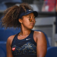 A butterfly lands on Naomi Osaka as she plays against Tunisia's Ons Jabeur during their women's singles match on Day 5 of the Australian Open in Melbourne on Friday. | AFP-JIJI
