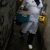 A health care worker carrying a cooler containing doses of Sinovac's coronavirus vaccine, walks along an alley during a visit to senior citizens who cannot leave their homes, in Rio de Janeiro's Rocinha slum on Friday. | REUTERS