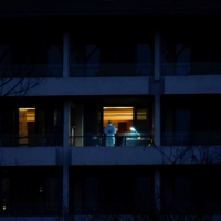 A medical worker stands on the balcony of a hotel where members of the World Health Organization team tasked with investigating the origins of COVID-19 were staying in Wuhan, China, on Feb. 3. | REUTERS