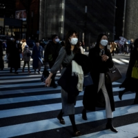 People wearing face masks cross a street in Tokyo earlier this month. | AFP-JIJI