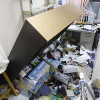 A bookshelf is seen tipped over at a home in Koriyama, Fukushima Prefecture, late Saturday after a powerful earthquake struck the region. | KYODO
