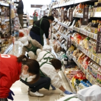 Employees wipe the oil-stained floor of a supermarket in Kunimi, Fukushima Prefecture, on Sunday following the previous day's magnitude 7.3 earthquake off Japan's northeastern coast. | KYODO