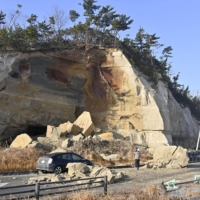 Fallen rocks near a roadside cliff in Soma, Fukushima, the day after a magnitude 7.3 earthquake hit northeastern Japan. |  崩落した岩が道路をふさいだ現場=14日午前8時10分、福島県相馬市