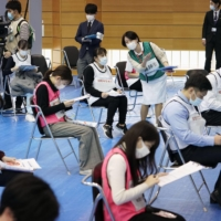 Participants in a vaccination drill for the novel coronavirus wait at Fujita Health University in Aichi Prefecture on Friday. | KYODO