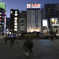 Few people are seen in front of Shimbashi Station in Tokyo on Saturday evening amid the coronavirus pandemic.   KYODO