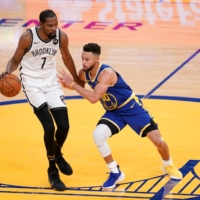 Brooklyn forward Kevin Durant dribbles against Warriors guard Stephen Curry on Saturday in San Francisco. | USA TODAY / VIA REUTERS