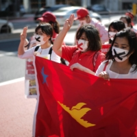 People march in the streets in Tokyo's Shibuya Ward on Sunday to protest the military coup in Myanmar. | RYUSEI TAKAHASHI