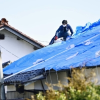 Men cover the damaged roof of a house with a blue sheet in Shinchi, Fukushima Prefecture, on Sunday. | KYODO