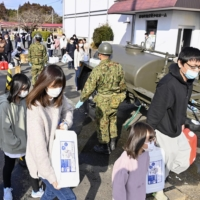 People receive water from the Self-Defense Forces in Shinchi, Fukushima Prefecture, on Sunday after the town suffered severe supply cuts following a strong quake the previous day. | KYODO
