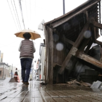 A woman walks past a damaged gate in the town of Kori, Fukushima Prefecture, in the rain on Monday. | KYODO