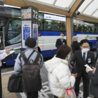 People try to board a JR Bus Tohoku Co. expressway bus in Sendai on Monday, as train services remained suspended. | KYODO