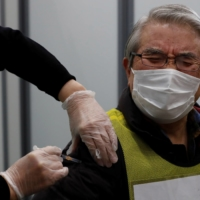 A participant pretends to receive a COVID-19 vaccine shot during a mock inoculation exercise in Kawasaki on Jan. 27. | REUTERS