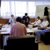 Manabu Yoneshima and other doctors attend a biweekly briefing about the COVID-19 situation at Municipal Tsuruga Hospital in Fukui Prefecture on Feb. 8.   REUTERS