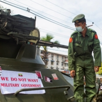 A soldier looks at a banner attached to a military vehicle outside Myanmar's Central Bank during a protest against the military coup in Yangon on Monday.  | REUTERS