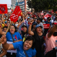 Protesters take part in a demonstration against the military coup in front of the National League for Democracy (NLD) office in Yangon on Monday.  | AFP-JIJI