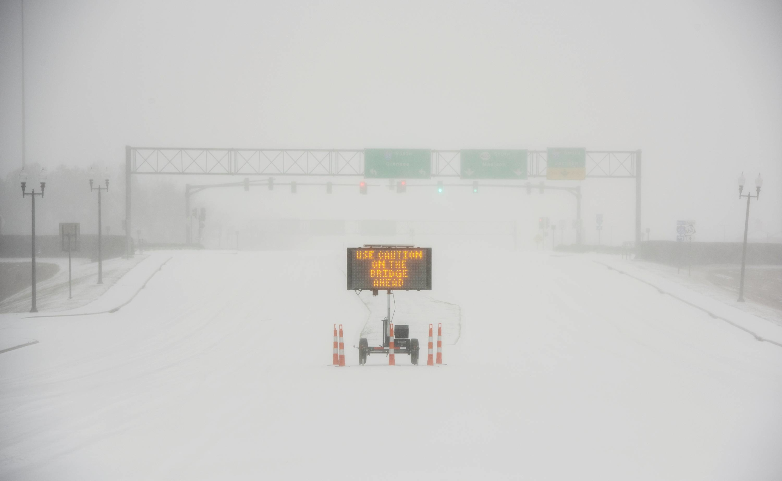 A sign warns motorists after a sudden heavy bout of snow and frozen rain on MS Highway 463 in Madison, Mississippi, on Monday.   | BARBARA GAUNTT / CLARION-LEDGER / USA TODAY NETWORK / VIA REUTERS