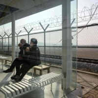 An elderly couple drink coffee next to a barbed wire fence at the Imjingak tourist park beside the civilian buffer zone that leads to the Demilitarized Zone separating the two Koreas, in Paju, north of Seoul, on Friday. | AFP-JIJI