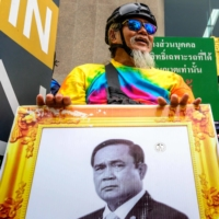 A pro-democracy protester holds a portrait of Thai Prime Minister Prayut Chan-ocha during a demonstration in Bangkok on Jan. 25. | AFP-JIJI