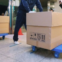Boxes containing COVID-19 vaccines arrive at a hospital in Tokyo on Tuesday prior to the start of vaccinations Wednesday morning. | POOL / VIA KYODO