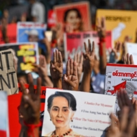 Protesters hold up the three finger salute with signs calling for the release of detained Myanmar civilian leader Aung San Suu Kyi during a demonstration Tuesday in Yangon against the military coup. | AFP-JIJI