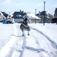A man walks to his friend's home in a neighborhood without electricity as snow covers Pflugerville, Texas, on Monday.  | AUSTIN AMERICAN-STATESMAN / USA TODAY NETWORK / VIA REUTERS