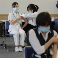 Medical workers receive a COVID-19 vaccine at the National Hospital Organization Tokyo Medical Center in Tokyo on Wednesday. | POOL