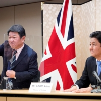 Japanese Foreign Minister Toshimitsu Motegi (left) and Defense Minister Nobuo Kishi take part in a video conference with their British counterparts at the Foreign Ministry in Tokyo on Feb. 3. | REUTERS