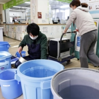Water filled buckets are placed in front of Miyagi Hospital in Yamamoto, Miyagi Prefecture, Tuesday following a water outage caused by Saturday's earthquake. | KYODO