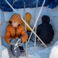 Avett Archibad, 8, helps his brother Sanders, 6, and sister Luella 10, build an Igloo in their front yard of their home in the Blackhawk neighborhood in Pflugerville, Texas, on Tuesday.    AMERICAN-STATESMAN / USA TODAY NETWORK / VIA REUTERS