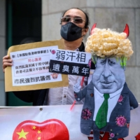 A caricature of British Prime Minister Boris Johnson is displayed by pro-Beijing activists as they gather outside the British Consulate-General to protest against the use of the British National (Overseas) passport in Hong Kong on Feb. 1. | AFP-JIJI