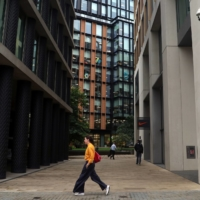 A woman walks past a surveillance camera in the Kings Cross area in London. | REUTERS