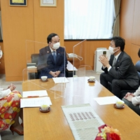 Tetsushi Sakamoto (center, left), tapped to be the minister of loneliness by Prime Minister Yoshihide Suga, discusses the issue with Yuichiro Tamaki (center, right), leader of the Democratic Party for the People, in the Cabinet Office on Feb. 15. | KYODO