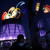 A man wearing a face mask walks near the lit-up Olympic rings at the top of the Olympic Tower, a year ahead of the opening of the 2022 Winter Games, in Beijing on Feb. 4. | REUTERS