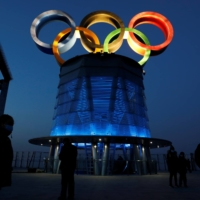 People wearing face masks walk near the lit-up Olympic rings at the top of the Olympic Tower, a year ahead of the opening of the 2022 Winter Games, in Beijing on Feb. 4. | REUTERS