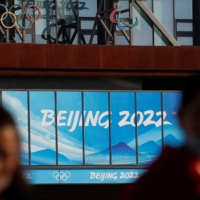 People wearing face masks walk near the office complex of the Beijing Organising Committee for the 2022 Winter Games, a year ahead of the opening of the Olympics in Beijing on Feb. 4. | REUTERS