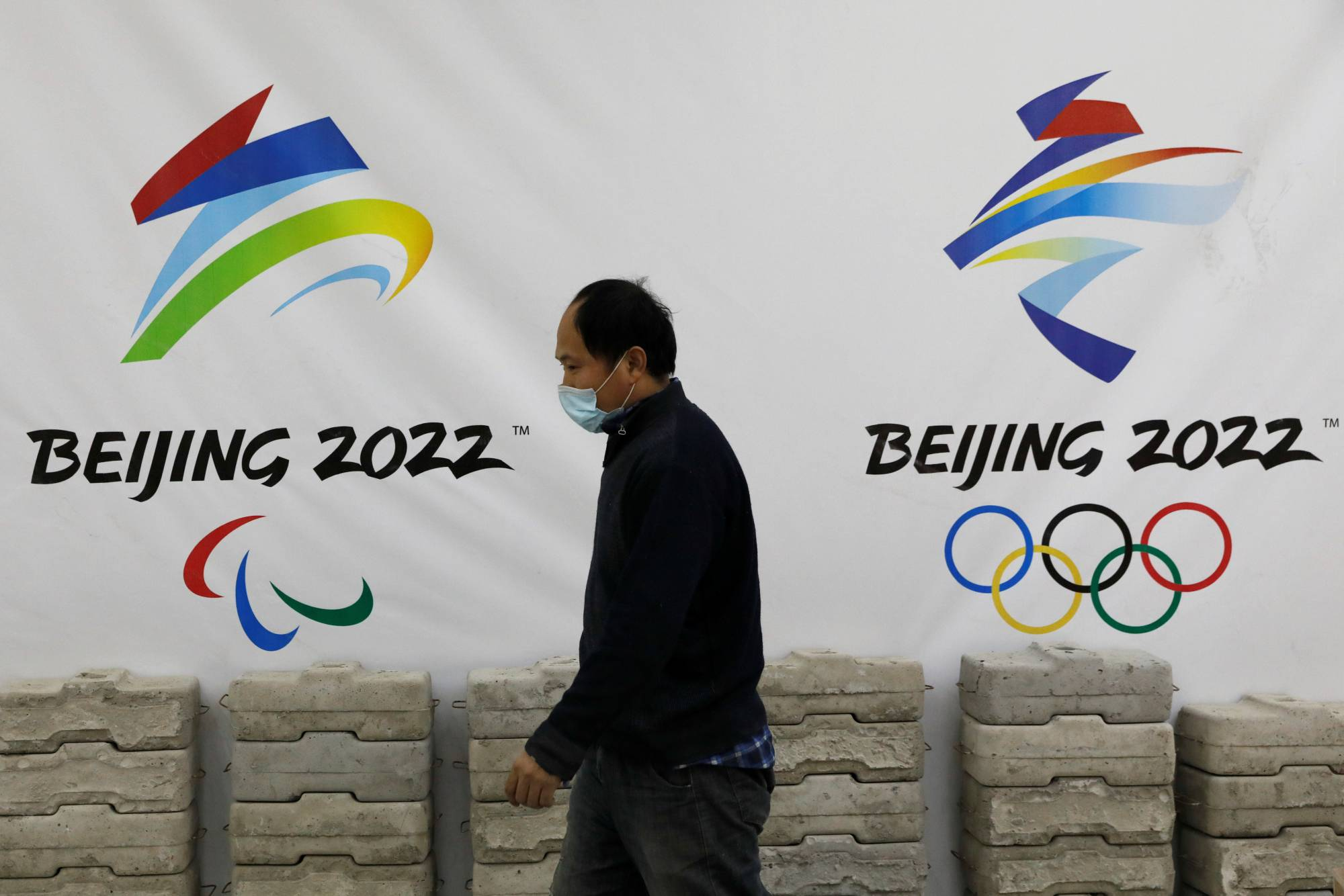 A man walks past a board with logos of 2022 Winter Olympic Games at a souvenir shop under renovation in Beijing on Jan. 29. | REUTERS