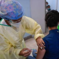 A health worker applies a dose of the Sputnik V vaccine against COVID-19 to a staff member of the University Clinical Hospital in Caracas on Friday amid the novel coronavirus pandemic. | AFP-JIJI