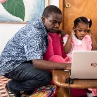 Jean Romuald Ernest, 47, helps his daughter Lucie reconnect to the internet as she takes classes through remote learning on Feb. 18 in Port-au-Prince, Haiti.  | AFP-JIJI