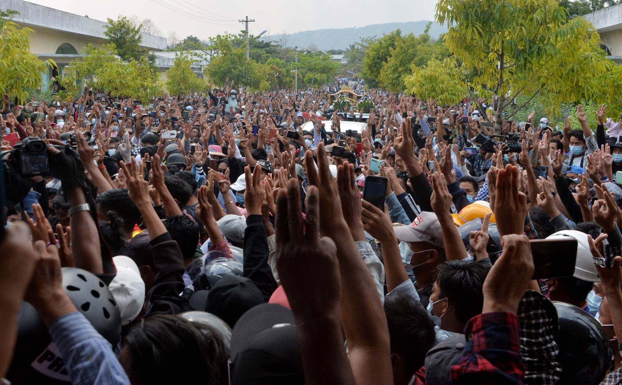 Protesters hold up three-finger salutes as they pray for Mya Thwate Thwate Khaing, who died after being shot at a protest against the military coup, in Naypyidaw on Sunday.    AFP-JIJI