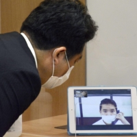 A video telephone interpretation system is demonstrated at the Foreign Residents Support Center in Tokyo on July 6, 2020. Hosting the offices of eight public organizations, the support center opened the same day to provide foreign residents in Japan with advice on employment, visas, laws and humanitarian issues in 11 languages. | KYODO