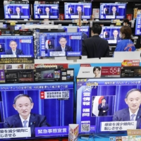TV screens at an electronics store show Prime Minister Yoshihide Suga speaking at a news conference on Jan. 13 to declare a coronavirus state of emergency in seven additional prefectures, including Aichi, Fukuoka and Osaka. | KYODO