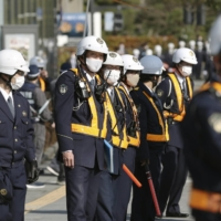 Police officers are seen Monday outside a hall in Matsue, Shimane Prefecture, where a Takeshima Day ceremony was held.  | KYODO