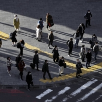 Pedestrians wait to cross a road in the Shibuya district of Tokyo last week. The capital is said to still be experiencing a 'severe' COVID-19 infection situation. | BLOOMBERG
