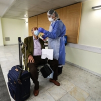 A health worker takes a nasal swab from a passenger for a COVID-19 test upon his arrival from Tunis, Tunisia, at Nice Airport in France. | AFP-JIJI