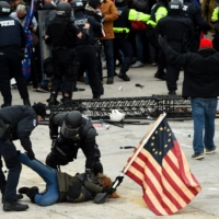 Police detain a person as supporters of Donald Trump riot outside the Capitol in Washington on Jan. 6.    AFP-JIJI
