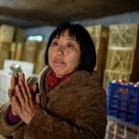 Farmer Xiang Xiuli, 53, is interviewed at her warehouse stocked with crates of oranges in Baojing county, in central China's Hunan province.  | AFP-JIJI