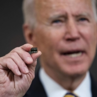 U.S. President Joe Biden displays a semiconductor at the White House on Wednesday before signing an executive order intended to insulate the American economy from future shortages of critical imported components. | DOUG MILLS / THE NEW YORK TIMES